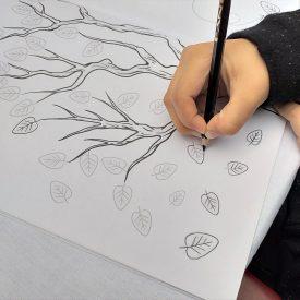 Dječak crta linije lišća na drvetuu