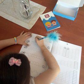 Djevojčica vježba pisanje ravnih i horizontalnih linija